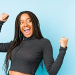 Young,African,American,Woman,Isolated,On,Blue,Background,Raising,Fist